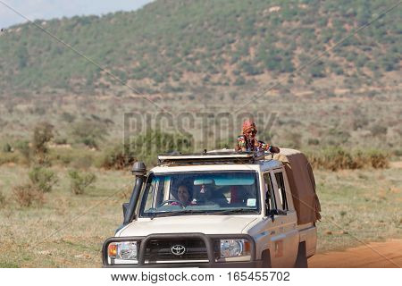 SAMBURU NATIONAL RESERVE KENYA - NOVEMBER 27 2016: A Samburu safari guide looking for animals for a visitor on an open top safari vehicle