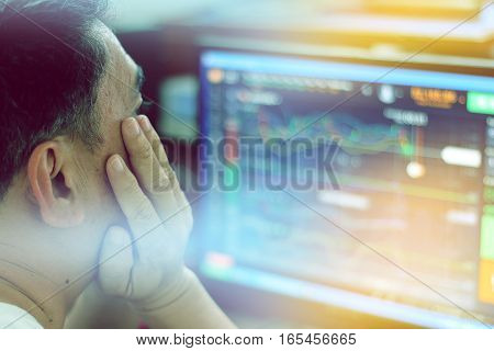 trader is looking at financial charts on the computer monitor