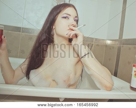 Sexy girl posing in a bath with cigarette and wine