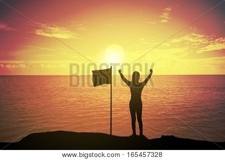 silhouette of winning success woman at sunset or sunrise standing and raising up her hand near the flag in celebration of having reached mountain top summit goal.Happy celebrating.business success concept