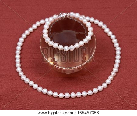 Freshwater white pearl necklace and crystal ball on red fabric background