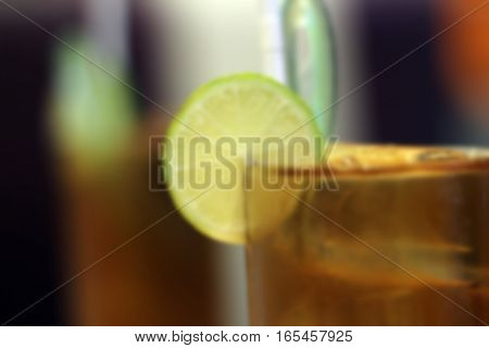 blurred glasses of iced tea with lemon slices background