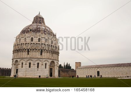 PISA ITALY - JANUARY 23 2016: The baptistery in Campo dei Miracoli during a cold day of winter with many tourists visiting.