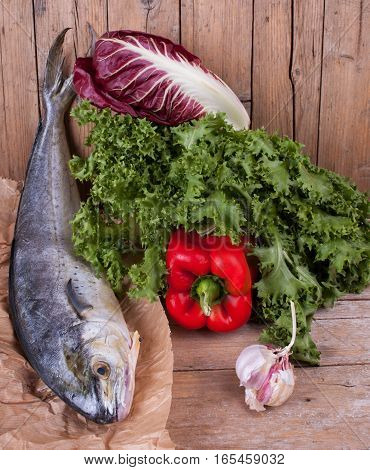 Raw lampuga fish with fresh lettuce bell pepper chicory and garlic ingredients for a healthy mediterranean cuisine.
