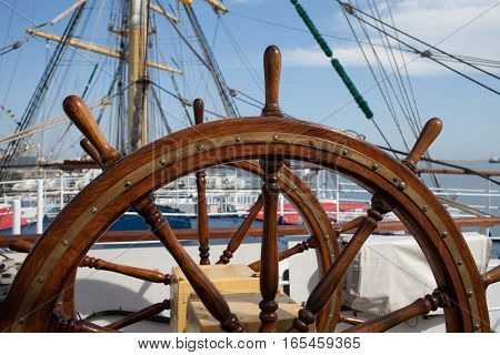 Old wooden steering wheel on sailing ship.