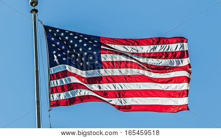 An American flag is flapping in the wind on a bright summer day.
