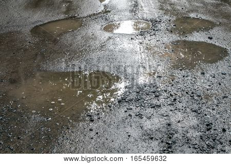 Dirty puddles on an unpaved road .