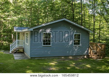 Blue house in a shady wooded area.