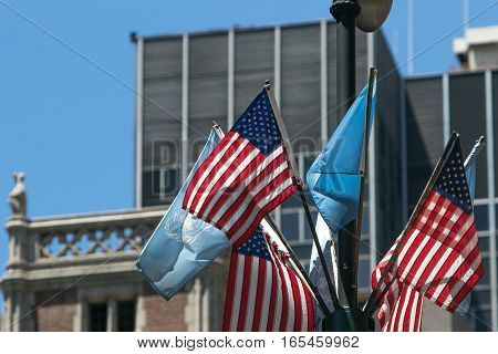 Small American and UN flags flying on a lamp post.