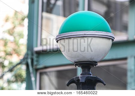 A green and white subway entrance orb lamp.