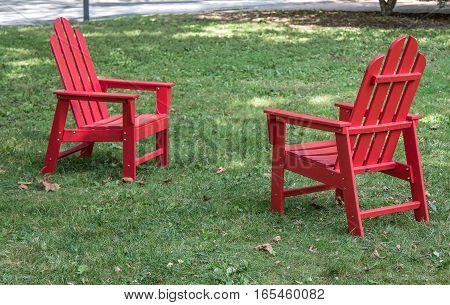 Two red wooden chairs stand on a lawn.