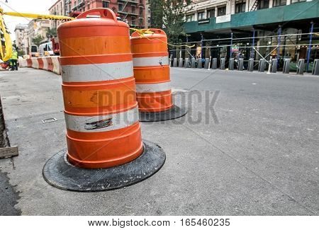 A traffic barricade of orange barrels indicates a site of road construction work in Manhattan.