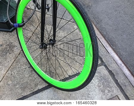 A chained bicycle's colorful green front wheel.