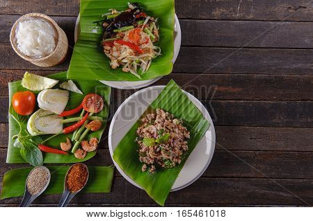 spicy minced pork salad on fresh banana leaf and ingredient