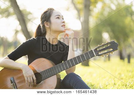 Young attractive asian woman playing acoustic guitar