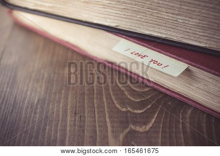 Stack of Old Book with Bookmarks I love you writing on Wooden Background in Vintage Tone
