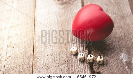 Valentine Day with Heart and word Love on Wooden Background in Vintage Tone