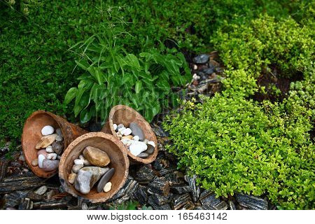 In a flower bed three ceramic cones and different small stones are used as decorative elements.