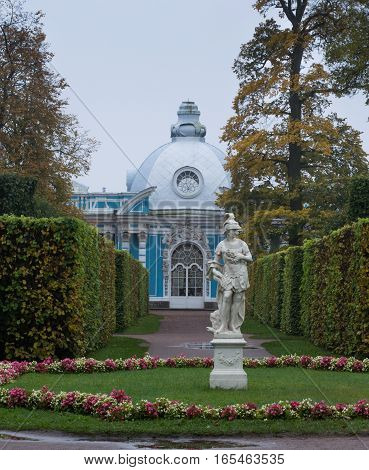 Statue of Apollo surrounded by grass and flowers with path leading to blue and white building on the grounds of Catherine's Palace near St. Petersburg, Russia
