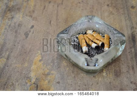 A dirty ashtray with cigarette ash and butts on dirty wooden