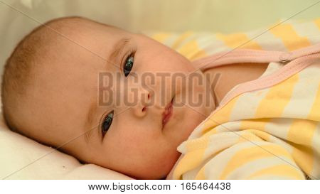 Little newborn baby lying in his bed close-up portrait
