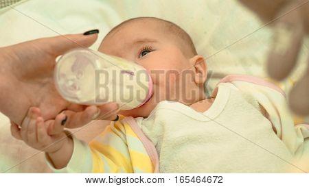 Little newborn baby drinking milk from a bottle close-up