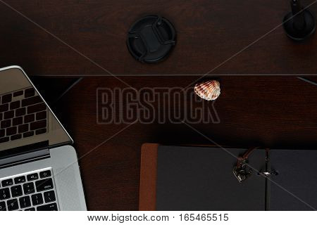 Wooden desk with laptop and open empty journal