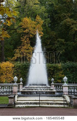 Pyramid Fountain in the Peterhof Gardens with a dirt path and stone steps leading to it. The fountain is surrounded by stone banisters and deciduous trees with fall foliage.  Located near St. Petersburg Russia.