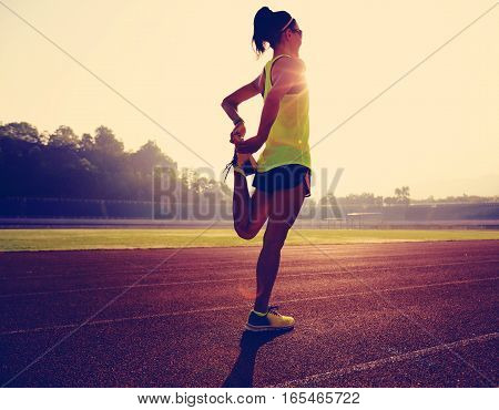 young fitness woman runner stretching legs on stadium track