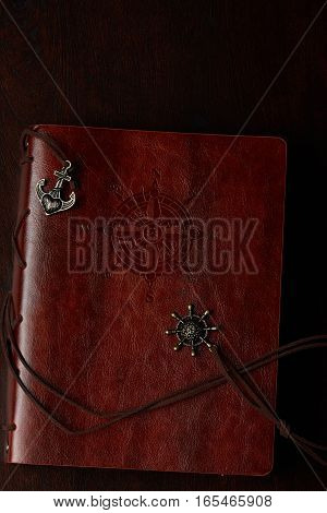 Brown leather book cover with travel compass decoration