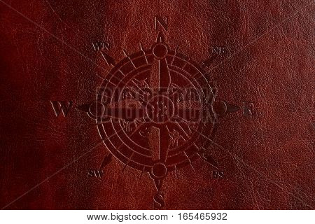 Compass print on brown leather cover closeup. East west south north sides