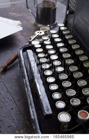 Antique typewriter on a vintage table with an old wooden surface