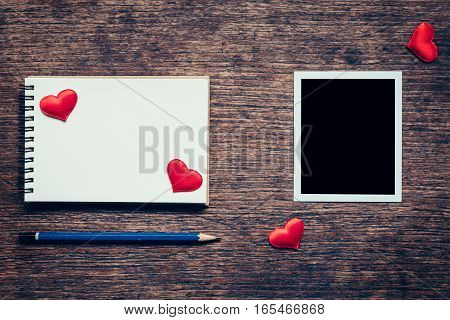 Blank Photo Frame, Notebook, Pencil And Red Heart On Wood Table Background.
