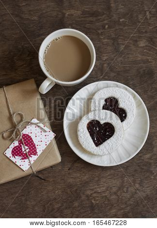 Valentine's day romantic breakfast. Cookies-hearts with jam coffee and a gift in craft paper on a wooden table top view. Flat lay