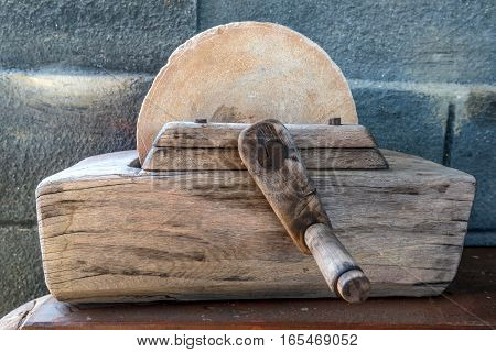 Close-up of old primitive grinding stone with wooden mechanism