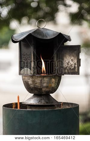 Traditional oil lamp lit at the buddhist temple.