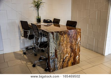 Office table made from brown exotic grain granite counter. Porcelain floor tiles in staggered pattern. Background wall white marble tiles. Marble, Granite, Tile, Counter