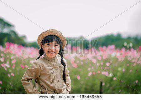 Beautiful child flower in sumer park. Happy kid having fun outdoors.