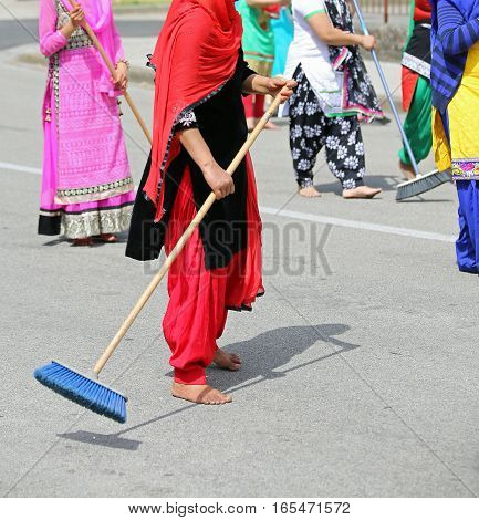Many Barefoot Women With Colorful Clothes Sweep The Paved Road A