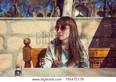 Young Woman With Sunglases And Long Hair Is Seating On A Bench In Street Cafe, Bukhara, Uzbekistan