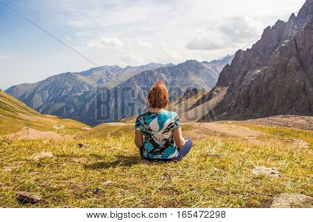 Aged Woman Are Sitting In Yoga Style And Looking Into The Distance At The Mountains, Tien Shan Mount
