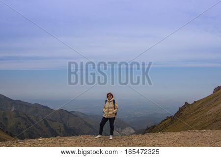 Aged sport woman in sunglass are standing at Talgar pass Tien Shan mountains near Shymbulak ski resort Almaty Kazakhstan 2016