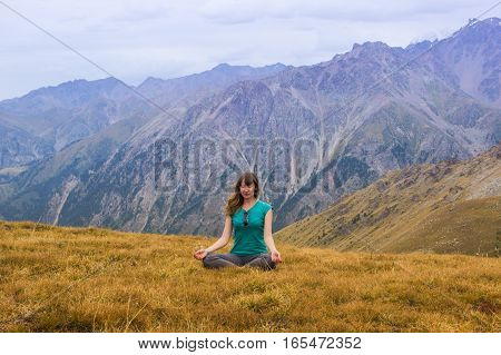 Woman Are Sitting In Yoga Style At The Mountains, Tien Shan Mountains Near Shymbulak Ski Resort, Alm