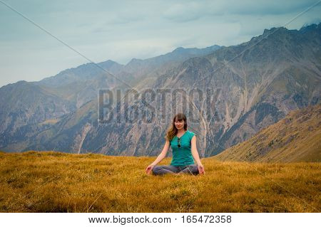 Woman Are Sitting In Yoga Style And Looking Into The Distance At The Mountains, Tien Shan Mountains