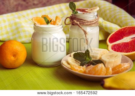 .organic Homemade Sweet Milk Dessert With Banana, Cinnamon, Tangerine, Red Orange And Mint On The Wo