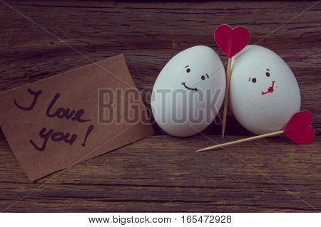 .the Love Of Two Eggs, Red Hearts And Card With Text I Love You On Wooden Background