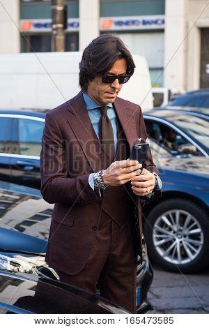 MILAN ITALY - JANUARY 15: Fashionable man poses outside Ferragamo fashion show building during Milan Men's Fashion Week on JANUARY 15 2017 in Milan.