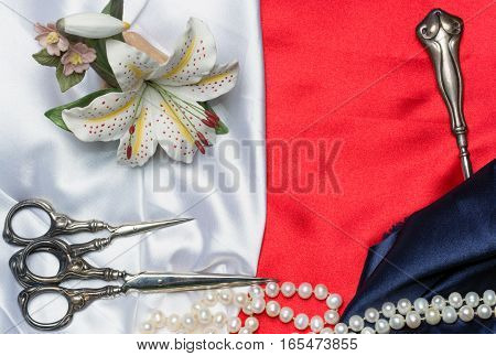 Antique sewing tools, porcelain lily and a pearl necklace on a silk cloth