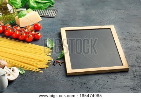 Blank board chalk with ingredients for cooking Italian pasta on dark stone surface