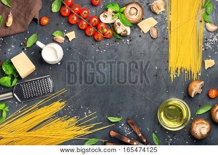 Frame of raw spaghetti with a set of ingredients for cooking pasta on a dark surface top view